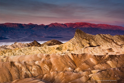 """Badlands of Zabriskie Point"" Location: Death Valley National Park, California.  These are eroded badlands of death valley national park seen from Zabriskie point at sunrise. The type of soil and extreme dryness of death valley makes plant life impossible. The hues come from mineral deposits in the soil. The first rays of light at sunrise illuminate the Panamint mountains on the other side of the valley.  Tech Info and Tip: Lens: Canon EF 24-70mm f/2.8L @ 38mm Camera: Canon EOS 30D Exposure: 1sec at f/22 and ISO 100 Filters: SinghRay 3 stop hard edge ND grad  I have only been here during the month of Dec when the sun rises from behind where I was standing. It looks like a nice vantage point during sunrise possibilities here and endless.   Death Valley has such unique landscape that defies imagination. A visit here is the closest thing to vising an alien landscape. It is one of the most popular locations to photograph. Its badlands, sand dunes, salt pans, strange racetracks offer unique opportunities to capture its beauty."