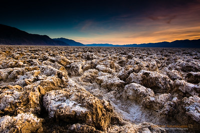 """Salt formations at Devil's Golf Course"", Location: Death Valley National Park, California. [Map/GPS]  When an ancient lake dried up 10 thousand years ago it left massive salt deposits on the lake bed. The salt and minerals get washed away from the mountains and continue to get deposited in the death valley lake beds even today. This is a late evening picture of the strange landscape with sunset happening behind Panamint mountains.  Tech Info and Tip: Lens: Canon EF-S 10-22mm f/3.5-4.5 @ 16mm Camera: Canon EOS 30D Exposure: 0.8 sec at f/20 and ISO 100 Filters: SinghRay 3 stop hard edge ND grad  The colors of the landscape here can change so much depending on the time of the day. I first arrived here during mid noon when this particular spot looked dry and dull but when I returned during sunset the rich colors could be captured after using the ND Grad filter.  Death Valley has such unique landscape that defies imagination. A visit here is the closest thing to vising an alien landscape. It is one of the most popular locations to photograph. Its badlands, sand dunes, salt pans, strange racetracks offer unique opportunities to capture its beauty."