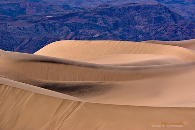 """Mesquite Sand Dunes"" Location: Death Valley National Park, California.  I always wanted to photograph the lines and patterns that form in sand dunes. So when I visited Death Valley I liked this spot from where sharp edges were looking well with the smooth undulations of the dunes and leading quite nicely to the mountains behind.  Tech Info and Tip: Lens: Canon EF 70-200 f/4L IS @ 180mm Camera: Canon EOS 30D Exposure: 1/100sec at f/8 and ISO 100 Filters: No filters  I typically prefer not to shoot during mid day lighting conditions, however, this particular shot came out nice even though it was shot during mid day conditions.  Death Valley has such unique landscape that defies imagination. A visit here is the closest thing to vising an alien landscape. It is one of the most popular locations to photograph. Its badlands, sand dunes, salt pans, strange racetracks offer unique opportunities to capture its beauty."