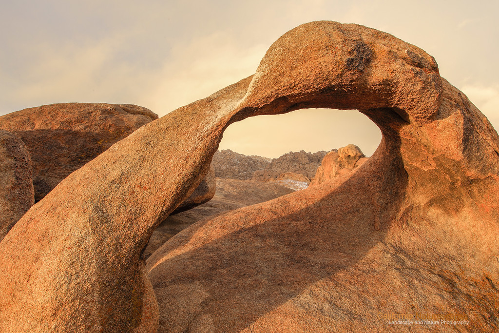 """Möbius Arch"" <br>Location: Alabama Hills, Lone Pine, California.  <p></p><p>Möbius arch is one of the most iconic rock formations on eastern sierra landscape, however, photographing it can get tricky. The name, as you may have guessed, derives from a mathematical concept of '<a href=""http://en.wikipedia.org/wiki/M%C3%B6bius_strip"">Möbius strip</a>'.  This is first of the series of few images of the arch where I liked the warmth of the morning light on the arch against winter fog in the background. On a clear day it is possible to see Mt. Whitney through the arch, which makes from another interesting image.  </p><p>Tech Info: <br>Lens: Canon EF 17-40mm f/4L @ 22mm <br>Camera: Canon EOS 5D Mk II <br>Exposure: 1/8sec at f/14 and ISO 50 <br>Filters: No filters.  </p><p>Note to first time visitors to the arch: <br>It can can difficult to find the arch, but I found <a href=""http://gibphoto.com/pages/tips/alabama_hills.html"">these directions</a> quite useful in locating it. Since you have to be here much before sunrise it is advisable to first go and find the arch the previous evening. Also winter is the best time to go here since low angle of the sun casts beautiful shadow of the arch and the light is sublime. And oh yes, get enough warm clothing, it can get quite cold there.  <br><br>One has to really visit eastern sierra landscapes to truly appreciate its beauty. I don't think any photograph can do the justice of what it feels to hike on barren landscapes, camp besides some of the most scenic lakes and feel out of breath at high altitudes. Over the years I have had a few chances to hike on eastern sierra mountains including Mt. Whitney, but only recently I began to photograph it. So here are few images from one of the most unique places on the Sierra-Nevada mountain range.</p>"