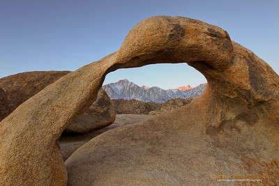 """First Light on Mt Whitney"" Location: Alabama Hills, Lone Pine, California.  On my second day of photoshoot at this location I saw this view of Mt. Whitney lit by the first rays of sunlight at dawn. My previous attempt at this location had Mt. Whitney shrouded in fog, so I was happy to finally get the view I came here to see.  It is quite an experience to shoot here. You have to arrive when it is still dark and hike up to this spot to claim a spot on the rock behind the arch. I read on the internet that this place can get very crowded since it is a classical sunrise spot to photograph. I, however, had this place pretty much to myself. On the contrary I enjoyed company of another fellow photographer Keith Kapple who was also there to photograph the arch. We chatted a bit and later drove around hunting for other arches in the area. It is always nice to bump into fellow photographers in the field. There are few more interesting arches here but I will leave those for my next trip here.  Tech Info: Lens: Canon EF 17-40mm f/4L @ 26mm Camera: Canon EOS 5D Mk II Exposure: 2sec at f/14 and ISO 50 Filters: No filters Post processing: The as-shot image needed warm tones since it was shot during dawn. Without adding warm tones the image can look excessively blue (cold color temp) One has to really visit eastern sierra landscapes to truly appreciate its beauty. I don't think any photograph can do the justice of what it feels to hike on barren landscapes, camp besides some of the most scenic lakes and feel out of breath at high altitudes. Over the years I have had a few chances to hike on eastern sierra mountains including Mt. Whitney, but only recently I began to photograph it. So here are few images from one of the most unique places on the Sierra-Nevada mountain range."