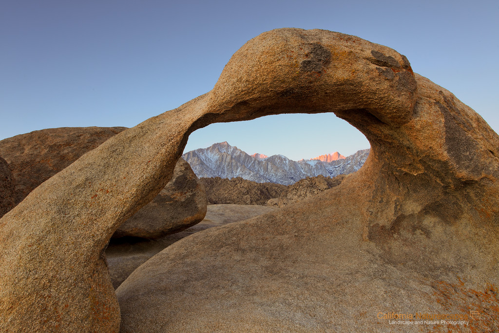 """First Light on Mt Whitney"" Location: Alabama Hills, Lone Pine, California.  On my second day of photoshoot at this location I saw this view of Mt. Whitney lit by the first rays of sunlight at dawn. My previous attempt at this location had Mt. Whitney shrouded in fog, so I was happy to finally get the view I came here to see.  It is quite an experience to shoot here. You have to arrive when it is still dark and hike up to this spot to claim a spot on the rock behind the arch. I read on the internet that this place can get very crowded since it is a classical sunrise spot to photograph. I, however, had this place pretty much to myself. On the contrary I enjoyed company of another fellow photographer <a href=""http://www.kapplemultimedia.com"">Keith Kapple</a> who was also there to photograph the arch. We chatted a bit and later drove around hunting for other arches in the area. It is always nice to bump into fellow photographers in the field. There are few more interesting arches here but I will leave those for my next trip here.  Tech Info: Lens: Canon EF 17-40mm f/4L @ 26mm Camera: Canon EOS 5D Mk II Exposure: 2sec at f/14 and ISO 50 Filters: No filters Post processing: The as-shot image needed warm tones since it was shot during dawn. Without adding warm tones the image can look excessively blue (cold color temp) <br><br>One has to really visit eastern sierra landscapes to truly appreciate its beauty. I don't think any photograph can do the justice of what it feels to hike on barren landscapes, camp besides some of the most scenic lakes and feel out of breath at high altitudes. Over the years I have had a few chances to hike on eastern sierra mountains including Mt. Whitney, but only recently I began to photograph it. So here are few images from one of the most unique places on the Sierra-Nevada mountain range."