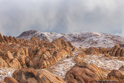"""Alabama Hills"" Location: Lone Pine, California.  I always wanted to visit Alabama Hills to see its strange rock formations, natural arches and views of Mt. Whitney. This is an early morning shot showing strange landscape. It had snowed the previous night and was about to snow again. You can see streaks of snowfall on the distant hills while early morning light illuminated the scene from the side. I loved how this image turned out.  Tech Info: Lens: Canon EF 70-200 f/4L IS @ 70mm Camera: Canon EOS 5D Mk II Exposure: 1/20sec at f/11 and ISO 3200  The light was changing fast and there was no time for me to setup the tripod, hence high ISO for hand-held shooting. Within few moments it was snowing in the whole area and the light that illuminated the rocks had gone.  One has to really visit eastern sierra landscapes to truly appreciate its beauty. I don't think any photograph can do the justice of what it feels to hike on barren landscapes, camp besides some of the most scenic lakes and feel out of breath at high altitudes. Over the years I have had a few chances to hike on eastern sierra mountains including Mt. Whitney, but only recently I began to photograph it. So here are few images from one of the most unique places on the Sierra-Nevada mountain range."