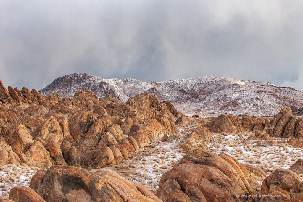 """Alabama Hills"" <br>Location: Lone Pine, California.  <p></p><p>I always wanted to visit Alabama Hills to see its strange rock formations, natural arches and views of Mt. Whitney. This is an early morning shot showing strange landscape. It had snowed the previous night and was about to snow again. You can see streaks of snowfall on the distant hills while early morning light illuminated the scene from the side. I loved how this image turned out.  </p><p>Tech Info: <br>Lens: Canon EF 70-200 f/4L IS @ 70mm <br>Camera: Canon EOS 5D Mk II <br>Exposure: 1/20sec at f/11 and ISO 3200  </p><p>The light was changing fast and there was no time for me to setup the tripod, hence high ISO for hand-held shooting. Within few moments it was snowing in the whole area and the light that illuminated the rocks had gone.  <br><br>One has to really visit eastern sierra landscapes to truly appreciate its beauty. I don't think any photograph can do the justice of what it feels to hike on barren landscapes, camp besides some of the most scenic lakes and feel out of breath at high altitudes. Over the years I have had a few chances to hike on eastern sierra mountains including Mt. Whitney, but only recently I began to photograph it. So here are few images from one of the most unique places on the Sierra-Nevada mountain range.</p>"