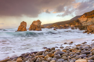 """Clearning Storm Over Garrapata"" Location: Garrapata State Beach, Monterey/Carmel Area, California.  Garrapata is one of my favorite spots to photograph and winter is the best time to photograph here. I love these iconic sea stacks and how the whole scene gets dramatic with some crashing waves and passing storm clouds.  Tech Info: Lens: Canon EF 17-40mm f/4L @ 37mm Camera: Canon EOS 5D Mk II Exposure: 0.4sec at f/16 and ISO 50 Filters: LEE ND Grads 0.9 and 0.6 soft edge stacked together Post Processing: A combination of dodge and burn in selective areas to bring out the details in both highlights and shadows. Added warm tones in Lightroom. Garrapata state park is one of the most photographed locations on the California coast. People are drawn to this spot due to the rugged coastline and its famous sea stacks. Just south of Monterey, California it is one of the best places to see waves crashing against the rugged coastline."