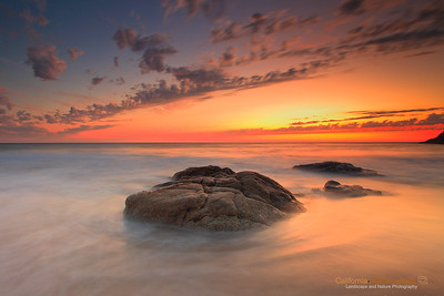 """Pacific Sunset"" Location: Graywhale Cove, San Mateo County, California.  A long exposure with minimalist composition was definitely the way to go for this image. The sunset light that was reflecting off the water was very subtle and using long exposure the water was rendered smooth and quiet adding to the mood of the image.  Tech Info and Tip: Lens: Canon 17-40mm f/4L @17mm Camera: Canon 5D Mk II Exposure: 15sec at f/16 and ISO 50 Filters: SinghRay 3 Stop ND grad hard edge to balance exposure of the sky and the foreground  An image shot directly facing the direction of the sun can often result in excessive contrast or dark areas. Using graduated neutral density filters I could ""even-out"" the exposures in the sky and land but that was not enough. By selectively working on the shadow areas in post processing I could obtain this image that resembled what I saw."
