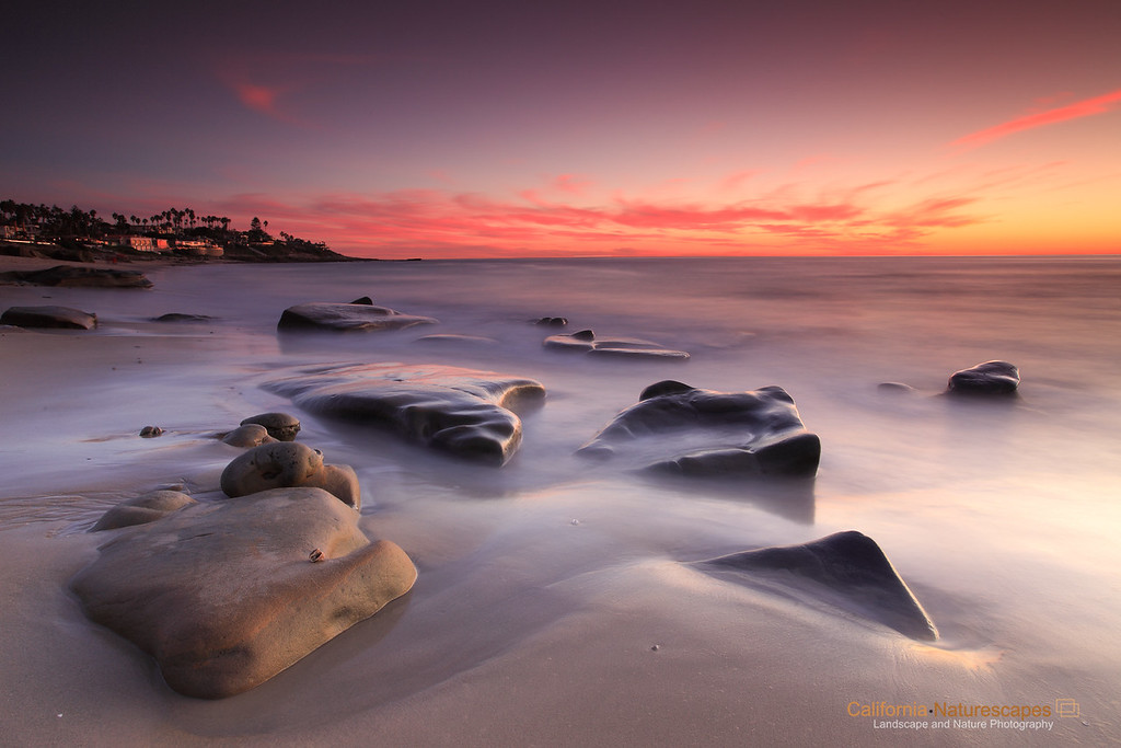 """La Jolla Sunset"" <br>Location: Wind and Sea Beach, La Jolla, California.  <p></p><p>I lived in La Jolla, California for about six years and had various evenings spent on this beach watching sunset. Unfortunately, I was not keen on photography then. So I had a chance to visit La Jolla again and I decided to capture a sunset shot I had in mind. I was glad that the light was great that evening and left a warm sunset glow on the rocks.  </p><p>In this image I used a long exposure to smooth out the waves and create a minimalist feel to mimic the calm I felt that evening.  </p><p>Tech Info: <br>Lens: Canon EF 17-40mm f/4 @ 22mm <br>Camera: Canon EOS 5D Mk II <br>Exposure: 50sec at f/14 and ISO 50 <br>Filters: LEE ND Grad 0.9 soft edge and Singh Ray 3 stop rev ND Grad along with Hoya 4 stop solid ND filter  </p><p>This image is pretty much straight out of the shutterbox. The colors are all real and captured during twilight glow of the sunset. ND filters allowed long exposure and balancing of the lighting conditions in the sky and foreground.  <br><br>La Jolla is one of the most beautiful coastal cities in the world. I have had a fortune to live there for several years, but unfortunately I never photographed it at that time. So on my recent visit to San Diego I decided to take time to shoot seascapes at the La Jolla coastline. I will be adding few more, so stay tuned.</p>"