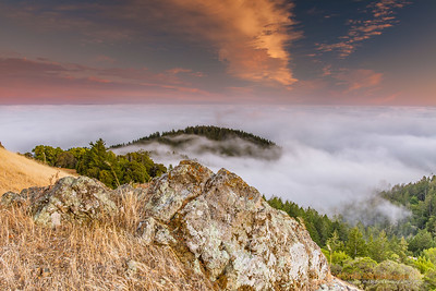 """Lichen Rock"" Location: Mt. Tamalpais, Mill Valley, California.  One of the most spectacular displays of nature in the San Francisco bay area is the fog rolling into the bay, and viewing it from the top of Mt. Tamalpais is like going to another world above the clouds. Also seen in the image are lichen covered rock and the golden grass that are so characteristic of the California landscape.  Tech Info and Tip: Lens: Canon 17-40mm f/4L @29mm Camera: Canon 5D Mk II Exposure: 2sec at f/11 and ISO 50 Filters: SinghRay 2 stop hard edge ND grad  I learnt recently that lichens were one of the first species to evolve on the planet giving rise to more complex plants. This place gives a sense of perspective where these lichens can be seen together with the giant redwoods at the foothills. San Francisco is a busy metropolitan area but just a few miles to the north exists a place so quiet and unique that it is such a perfect escape from the chaos of the city life. Mt. Tam, as it is locally know, is a perfect vantage point to watch the summer fog rolling into the bay or just enjoy the hike on its undulating hills and redwood forests."