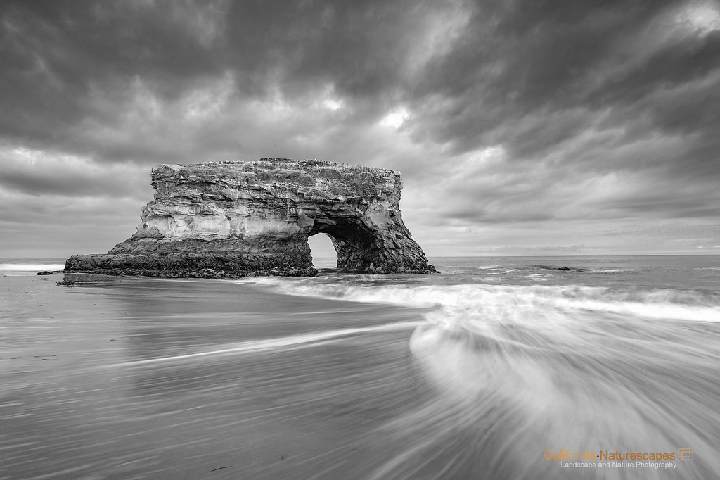 """The Beginning"" <br>Location: Natural Bridges State Beach, Santa Cruz, California.  <p></p><p>This is the last natural bridge standing along the shores of Natural Bridges State Beach in Santa Cruz. I have been photographing at this spot for years and what I found most difficult was to get a good combination of evening light and radiating clouds that would complement this natural wonder. On this particular day the clouds were spectacular. I further emphasized the mood of the scene using slightly long exposure to capture motion of the receding waves.  </p><p>Tech Info: <br>Lens: Canon EF 17-40mm f/4L @ 17mm <br>Camera: Canon EOS 5D Mk II <br>Exposure: 1sec at f/13 and ISO 100 <br>Filters: LEE ND Grads 0.9 and 0.6 soft edge  <br><br>Naturally formed bridges along the coastline of California are truly works of art by the erosive forces of water and wind. One of the best natural bridge exists on the aptly named Natural Bridges State Beach at Santa Cruz. These bridges form because crashing waves converge at a point and slowly erode away the rock creating a passageway. The erosion eventually destroys the bridge but new ones keep forming over a geologic time span of hundreds and thousands of years. In that sense these are transients, and like everything else that is beautiful in nature, these exist only for a short time... Go see them today!</p>"