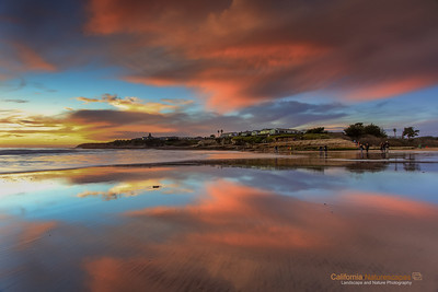 """Reflections: Last Sunset of 2012"" Location: Natural Bridges State Beach, Santa Cruz, California. Map   Tech Info: Camera: Canon EOS 5D Mk II Lens: Canon EF 17-40mm f/4L IS at 21mm Exposure: 0.8sec at f/14 and ISO 50 Filters: A 3-stop (0.9) and a 2-stop (0.6) LEE Graduated ND Filters stacked together Post Processing: Minimal post processing needed for this shot. Everything captured in single exposure.  Naturally formed bridges along the coastline of California are truly works of art by the erosive forces of water and wind. One of the best natural bridge exists on the aptly named Natural Bridges State Beach at Santa Cruz. These bridges form because crashing waves converge at a point and slowly erode away the rock creating a passageway. The erosion eventually destroys the bridge but new ones keep forming over a geologic time span of hundreds and thousands of years. In that sense these are transients, and like everything else that is beautiful in nature, these exist only for a short time... Go see them today!"