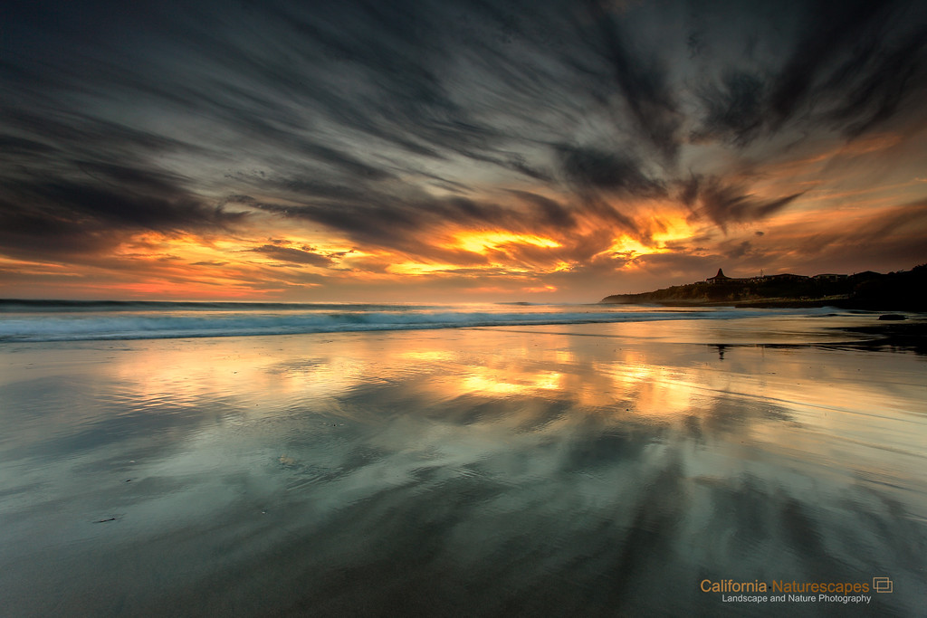 """Reflections"" <br>Location: Natural Bridges State Beach, Santa Cruz, California.  <p></p><p>A low tide and an awesome sunset along with interesting cloud formations careated perfect conditions to enjoy these reflections in the sand. Though this bridge is famous for its natural bridge, I often like to visit here just to see the reflections in the sand. The sand here retains the water long after the wave has receded allowing for spectacular displays of reflections.  </p><p>Tech Info: <br>Lens: Canon EF 17-40mm f/4L @ 17mm <br>Camera: Canon EOS 5D Mk II <br>Exposure: 1.3sec at f/13 and ISO 50 <br>Filters: LEE ND Grads  <br><br>Naturally formed bridges along the coastline of California are truly works of art by the erosive forces of water and wind. One of the best natural bridge exists on the aptly named Natural Bridges State Beach at Santa Cruz. These bridges form because crashing waves converge at a point and slowly erode away the rock creating a passageway. The erosion eventually destroys the bridge but new ones keep forming over a geologic time span of hundreds and thousands of years. In that sense these are transients, and like everything else that is beautiful in nature, these exist only for a short time... Go see them today!</p>"