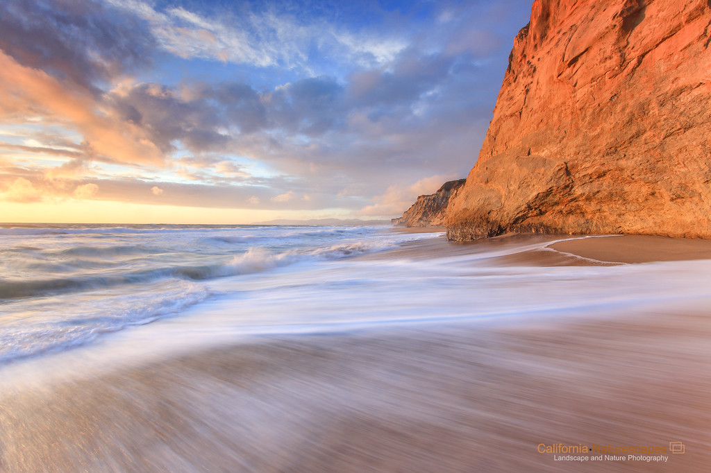 """Come Out Upon My Seas"" <br>Location: Pescadero State Beach, San Mateo County, California.  <p><p>The northern end of the Pescadero State Beach is dominated by these coastal bluffs. They rise up abruptly from the sand and tell a geological story that has shaped this landscape for thousands of years. It's a story of how the land here wass transformed by colossal forces within the earth. These forces first lifted certain parts of the landscape several hundred feet in the air and then gradually eroded them by the wind and the water. It's timeless and for me it is a place to find solitude. The day I shot this image an unusual storm was passing over Bay Area. It is always great to witness a passing storm which brings with it interesting cloud formations and filtered light that I so much strive to capture in an image.  <p>The combination of breaking storm, sunset light, texture on the face of the eroding bluff and receding wave finally gave me all the elements I needed to tell this geological story. This land is never the same. It changes with every tide and gets eroded evermore during every winter storm. As they always say, beauty is transient and this landscape certainly highlights that point.  <p>Tech Info: <br>Lens: Canon EF 17-40mm f/4L @ 17mm <br>Camera: Canon EOS 5D Mk II <br>Exposure: 1/2sec at f/13 and ISO 50 <br>Filters: LEE ND Grads 0.6 and 0.9"