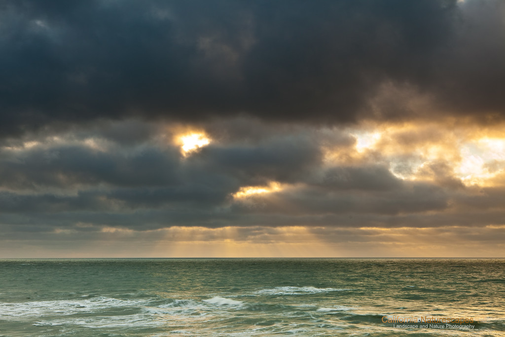 """Pescadero Sunset""<br /> Location: Pescadero State Beach, Pescadero, San Mateo County, California.<br /> <br /> The sunbeams peeking out of breaking storm clouds are always fun to photograph. Especially during a fast moving storm you can actually see the beams scanning the horizon... a truly awesome sight to see during winter months in California.<br /> <br /> Tech Info and Tip:<br /> Lens: Canon EF 24-70 f/2.8L at 50mm<br /> Camera: Canon 5D Mk II<br /> Exposure: 1/3sec at f/9 and ISO 50<br /> Filters: SinghRay ND Grads 3 stops hard edge<br /> <br /> The clouds that are not too dense and not too sparse make the best lighting in my limited experience shooting thse incredible sunbeams.g"