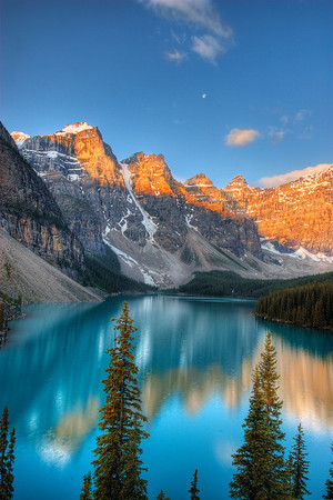 Classic scene at the rock pile of Moraine Lake in the Majestic Canadian Rockies. Look just above the mountain peaks and you can see a full moon sharing some time with natures sunrise.