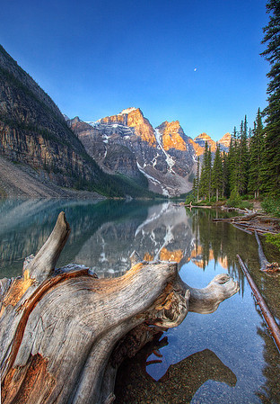 Sitting on a log at sunrise at Moraine Lake. If you look carefully into the distance above the mountains there is a full moon still peaking through!