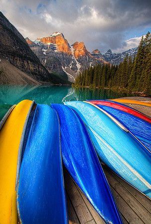 This photograph was taken at sunrise from the view of well worn canoes overlooking the ten peaks at Lake Moraine, Banff National Park in the Canadian Rockies. The interesting patterns on the bottom of the canoes are caused by years of gliding over the surface of  riverbed  rocks.