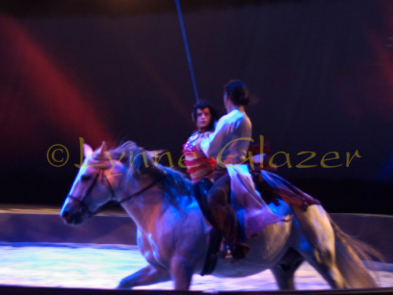 "In one of the most lyrical pieces, ""La Vida,"" two petite young women dressed in exotic and colorful gypsy costumes come out riding behind Pignon and another male rider, wearing flowing white shirts and black breeches, on their fairy-tale white steeds. The girls, attached discreetly to wires, dance with the men as they ride in circular forms, with the horses and each other in the air, swirling gently, slowly, ethereally, even upside down as in a Chagall painting."