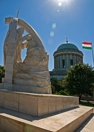 (SZENT ISTVçN MEGKORONçZçSA), ESZTERGOM<br /> SŸttoý limestone statue standing near the Basilica on the castle's round bastion. Mikl—s Melocco's nearly 12 metre-high work immortalises the moment when the crown is placed on the King's head.<br /> The twice life size figures and the arched stone ribs forming the frame are connected by a Cross. The composition shows coronation: the placing of the crown on the King's head.ÊThe formation suggests King Stephen's Admonitions to his son Prince EmericÊ(Imre herceg): Nothing raises you but humility...<br /> The two-figure statue group was unveiled on the anniversary of St Stephen'sÊdeath on the 15th August 2001.