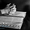 Praying with hands clasped seeking God with an open bible at red candle light and black and white background