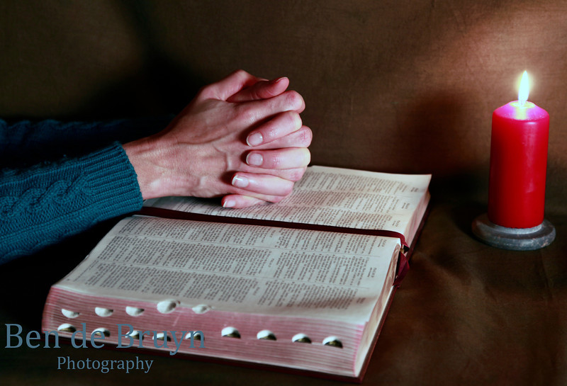 Praying with hands clasped seeking God with an open bible at red candle light and earth colored background