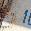 Number ten sign with old lock on white background with cracked paint and rust colors