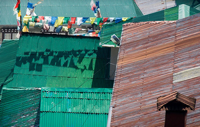 Namche - Nepal  Corrugated tin roofs, some painted, some rusted, overlap in a geometrical palette of metallic color and texture.  Namche, the trading and trekking hub of the Khumbu valley, has become a quickly growing community in the past 25 years, and includes electricity from both solar and hydroelectric sources.