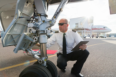 Pilot doing preflight check with tablet on Dassault Falcon 7x business jet. Jeff Bender. Honeywell Flight Operations, Phoenix, Arizona. GoDirect, HAPP, MPP.