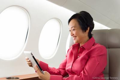 Business jet passenger using tablet in Dassault Falcon 7x cabin. Honeywell Flight Operations, Phoenix, AZ. GoDirect, HAPP, MPP.