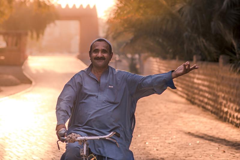 A happy man bikes through the oasis at dawn. Al Ain, UAE
