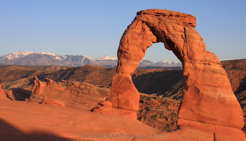 Utah's iconic Delicate Arch at sunset with the La Sal Mountains in the distance.