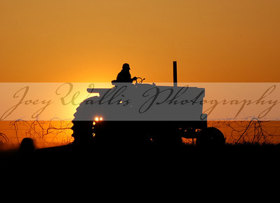 An unidentified farmer plants seed at sunset  near St. Donatus, IA., on May 17th, 2003.