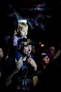 A young fan watches the concert intently while her father looks on.