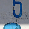 Number five faded paint in blue and blue oval shape on white weather worn background