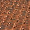 Interesting pattern with symmetry and flow of clay tiles rows on house roof