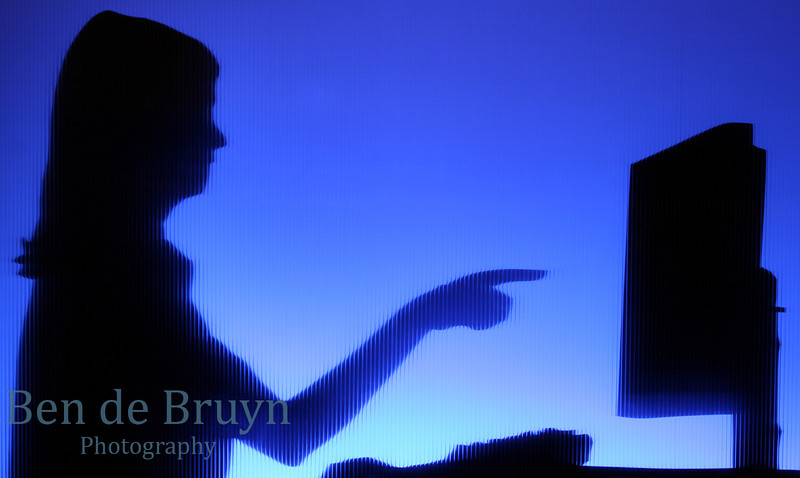Working late with woman at desk pointing at computer monitor of a desktop computer