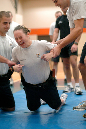ALL - The Law Enforcement Academy at Kalamazoo Valley Community College is a 17-week program that costs $3700.  Cadet Angel Merren gets hit with 50,000 volts of electricity during Tazer gun training as her fellow cadets hold her at the KVCC gym.