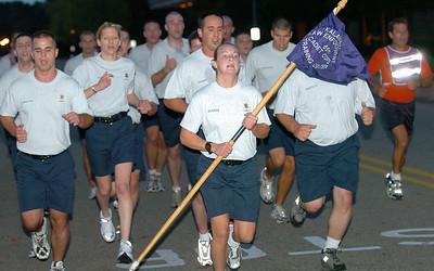 Cadet Merren carries the flag and leads the class on a 5-mile early morning run.   At right is Drill Sergeant Todd Christiansen.  Merren was chosen to be the guide-on bearer, carrying the flag and representing the entire class.