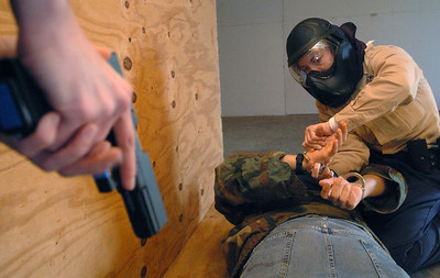 Cadet Merren handcuffs a suspect as partner Tracie Noe provides cover during a building scenario.