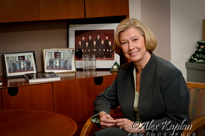 Corporate headshot of a woman with short blond hair wearing a gray and green outfit sitting in a chair with pictures in frames in the background smiling for the camera  Alex Kaplan Photographer https://professionalheadshots.com