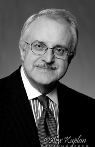 Black and white corporate headshot of a man with a mustache wearing a pinstriped jacket, button down shirt, tie and glasses smiling for the camera Alex Kaplan Photographer https://professionalheadshots.com