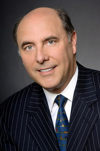 Corporate headshot of a man in a blue pinstripe suit jacket with a blue tie smiling for the camera by Alex Kaplan, photographer http://www.alexkaplanphoto.com