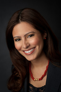 Corporate headshot of woman with brown hair and brown eyes wearing a black blazer, red necklace and red earrings smiling for the camera  by Alex Kaplan, photographer http://www.alexkaplanphoto.com