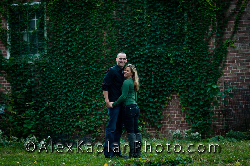 "Couple both wearing jeans and green shirts hugging each other and standing in front of a brick wall covered in ivy looking at the camera smiling by Alex Kaplan, photographer <a href=""http://www.alexkaplanphoto.com"">http://www.alexkaplanphoto.com</a>"