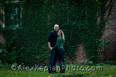 Couple both wearing jeans and green shirts hugging each other and standing in front of a brick wall covered in ivy looking at the camera smiling by Alex Kaplan, photographer http://www.alexkaplanphoto.com