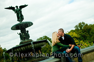 Couple sitting on the edge of a fountain holding each other while they share a kiss both wearing jeans and green shirts  by Alex Kaplan, photographer http://www.alexkaplanphoto.com