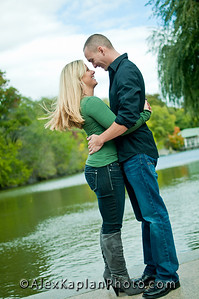 Couple both wearing jeans and green t-shirts hugging each other and smiling standing on the edge of water by Alex Kaplan, photographer http://www.alexkaplanphoto.com