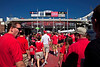 The sea of red converges on the stadium under perfect blue skies.