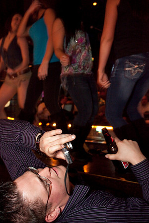 A patron leans back further to get the perfect shot of a little bar dancing.