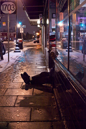 A man keeps warm by taking refuge on a stoop and passes the time by watching the night life along Baxter Avenue.