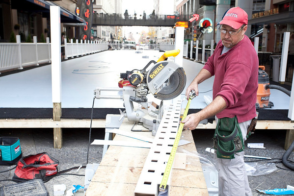 "Joe Olin of Realm Construction Company measures out a piece of the perimeter wall for the skating rink installed at Fourth Street Live on Monday. According to project superintendent John Turner, the rink measures ""one-hundred fifty-two feet by twenty-six feet"" and is constructed of ""synthetic panels that are coated with a liquid enhancer."""